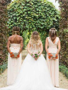 Photographe de mariage à courbevoie demoiselle d'honneur en ligne pose dans le parc des bagatelles à neuilly sur seines un bouquet dans le dos