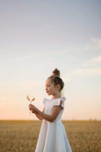 une enfant joue avec une fleur