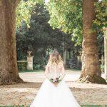 Photographe de mariage à courbevoie Photographe de naissance et mariage mariée de dos avec bouquet de fleur dans les mains parc des baguatelle neuilly sur seine