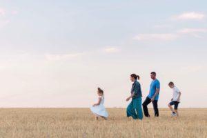 une famille marche dans u champs de blé