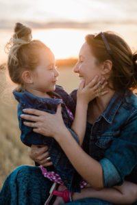 une maman prend sa fille dans ses bras